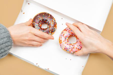 Foto de Female hands is taking colorful donuts. Hands is grabbing two last donuts in box on pastel background. - Imagen libre de derechos