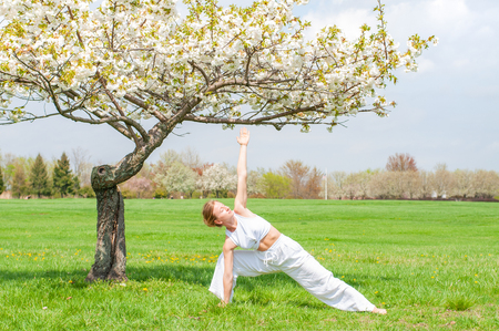 Photo pour Young woman is practicing yoga, doing Utthita Trikonasana exercise, extended triangle pose near blossom tree at the park. - image libre de droit