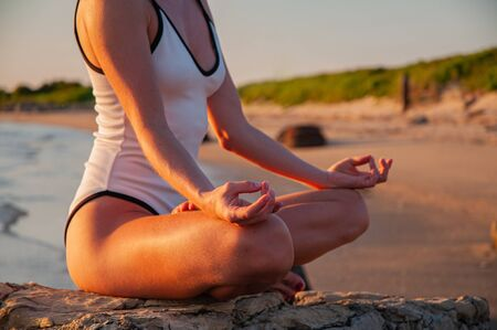 Woman is meditating on the calm beach at sunset. Woman is practicing yoga sitting in Lotus pose at sunrise. Silhouette of woman meditating on the beach
