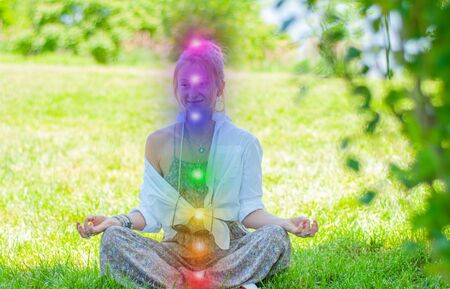 Foto de Happy woman is meditating in the lotus pose with glowing seven chakras on grass. Woman is practicing yoga on the park. Kundalini meditation. - Imagen libre de derechos