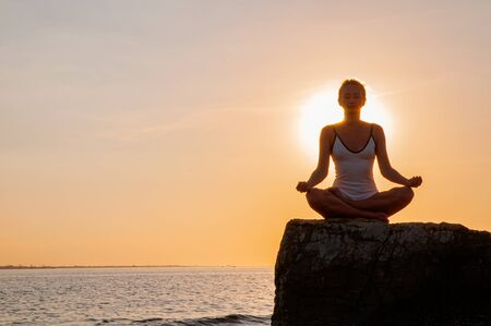 Woman is meditating on the calm beach at sunset. Woman is practicing yoga sitting on stone in Lotus pose at sunset. Silhouette of woman meditating on the beach