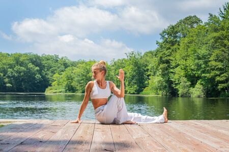 Photo pour Attractive woman is practicing yoga sitting in Ardha Matsyendrasana pose near lake. Young woman is meditating outdoors in morning. - image libre de droit