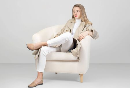 Photo pour Fashionable clothes. Beautiful fashion woman in trench coat and pant in studio - image libre de droit