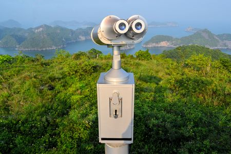 Coin operated telescope binoculars at a scenic lookout on the Vietnamese island Cat Ba, overlooking karst limestone rock islands in Halong Bay in the South China Sea