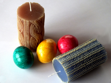 Two blue and brown candles with three eastereggs