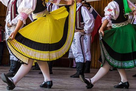 Young Czechs dancers in traditional costume perform folk dance.