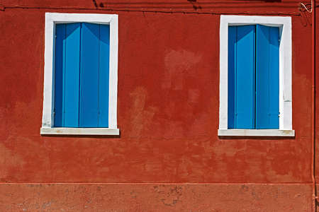 Building facade with wall painted in red and windows covered with wooden blinds blue. Burano, Italy.