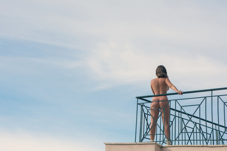 Naked female stands on the balcony