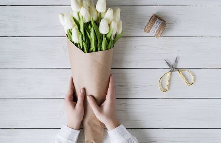 Photo pour Woman florist wrapping beautiful bouquet of white tulips in pack craft paper on the wooden table. Flat lay - image libre de droit