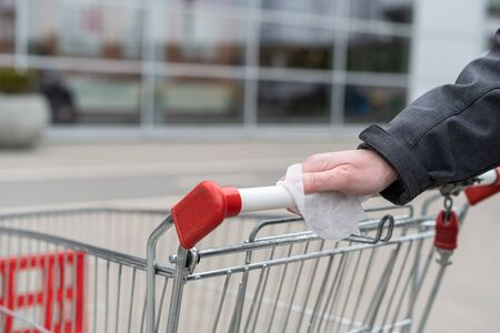 Photo pour Man cleaning handle of shopping cart, trolley using antivirus antibacterial wet wipe (napkin) for protect himself from bacteria and virus. grocery store, supermarket - image libre de droit