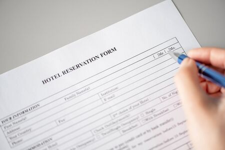 Photo pour Woman filling hotel reservation form putting check mark on Mrs. Reception desk. Hotel service, registration. Close up. Selective focus. - image libre de droit