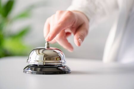 Photo pour Hand of guest ringing in silver bell. reception desk with copy space. Hotel service. Selective focus - image libre de droit