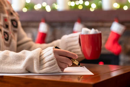 Photo pour Woman writing wish list using fountain pen on sheet of paper at christmas fireplace with decoration of light bulbs drinking hot chocolate and marshmallow. - image libre de droit