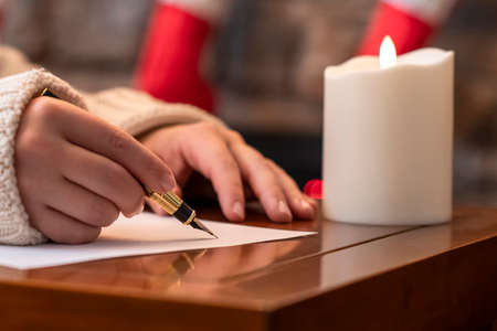 Photo pour Woman writing wish list using fountain pen on sheet of paper at christmas fireplace with decoration of light bulbs and candle on table. - image libre de droit