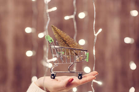 Photo for Woman holding out gold christmas tree in a small shopping cart through the glowing garland. Concept - Royalty Free Image