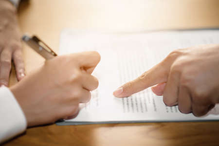 Photo pour The hand of a business man is using the index finger to let the customer sign the contract, contract, business agreement. - image libre de droit
