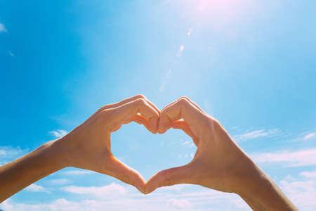 Photo pour Heart shape making of hands against blue sky - image libre de droit