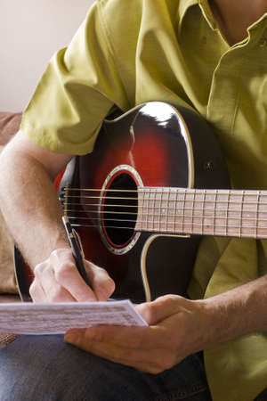 Songwriting on a red sunburst acoustic guitar