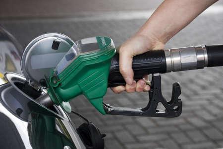 Hand holding green fuel pump refuelling a car