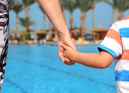 Mother and son holding hands on vacation looking at swimming pool concept for family vacations, child safety and single parent holiday