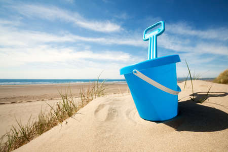 Childs bucket bucket and spade or sand pail and shovel at the beach on a sunny summer day