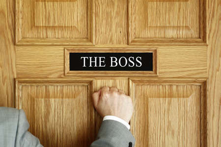 Businessman knocking on a door to The Boss office concept for meeting, trouble, problems, promotion or being fired