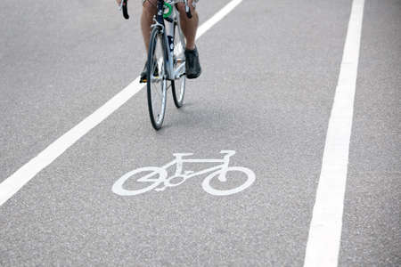 Commuter riding a bicycle on a city cycle lane or path across white painted bike symbol