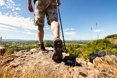 Hiker hiking on a mountain trail with distant views of countryside in summer sunshine