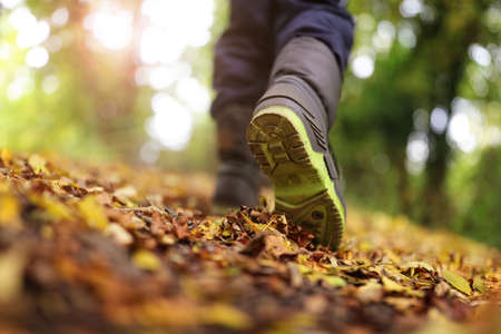Boy walking on footpath in autumn or winter concept for healthy lifestyle