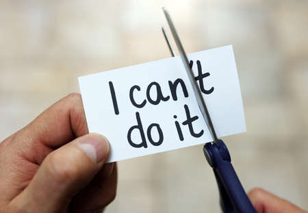 Man using scissors to remove the word can\'t to read I can do it concept for self belief, positive attitude and motivation