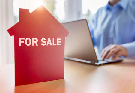 Man using laptop searching for real estate or new house on the internet with for sale sign on red house