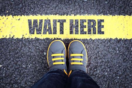 Photo pour Wait here feet queue behind yellow waiting line - image libre de droit