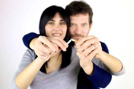 Man and woman breaking cigarette quitting smoke