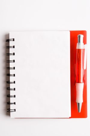 red notebook and ball point pen over white background