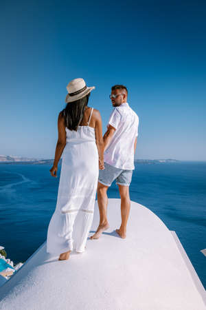 Photo for couple men and woman on vacation Santorini, View to the sea and Volcano from Fira the capital of Santorini island in Greece Europe - Royalty Free Image