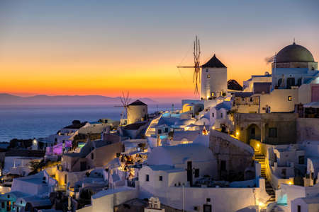 Photo for Sunset at the Island Of Santorini Greece, beautiful whitewashed village Oia with church and windmill during sunset, streets of Oia Santorini during summer vacation at the Greek Island - Royalty Free Image