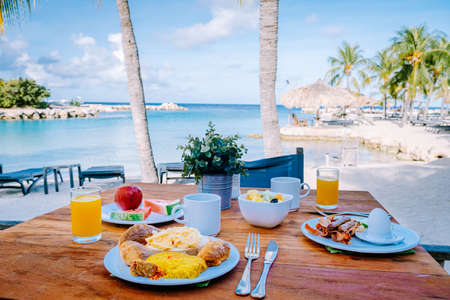 Photo pour breakfast on a table by the beach looking out over the ocean, Caribbean sea with breakfast table with coffee orange juice and croissants and fruit. bright scenery sunny day beach - image libre de droit