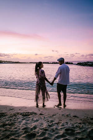 Photo for Curacao Willemstad, couple mid age Asian woman and European man on vacation at a luxury resort in Pietermaai , men and woman on the beach watching sunrise with beautiful orange pink sky - Royalty Free Image