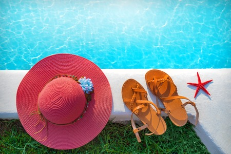 pool with clear turquoise water and a hat with shoes on the shore