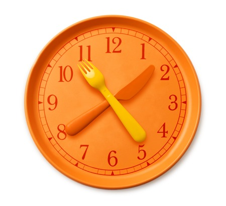 Photo pour isolated watch on the orange plate, where instead of arrows yellow orange fork and knife. plastic utensils and clock on the table. concept of diet and health - image libre de droit