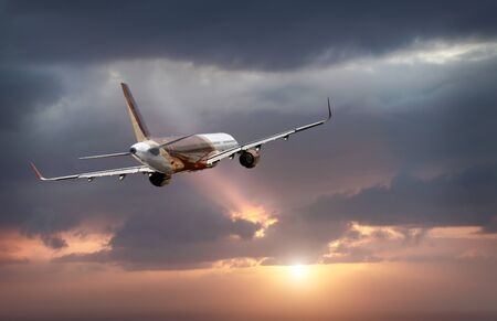 Photo pour passenger plane flying in the stormy dramatic sky. the sun shines from behind the clouds. the plane flies - image libre de droit