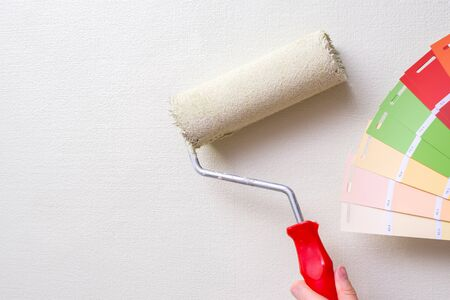 Foto de the painter holds the paint roller against the light wall and the color samples. the concept of repair in the apartment and painting the walls - Imagen libre de derechos