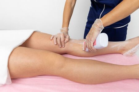 Photo pour beautician doing depilation of the legs of the client. slow motion. the client is lying on a pink couch - image libre de droit