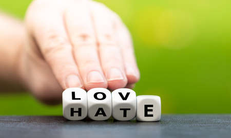 Photo pour Hand turns dice and changes the word hate to love. - image libre de droit