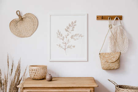 Photo pour Stylish korean interior of living room with brown mock up poster frame, elegant accessories, flowers in vase, wooden shelf and hanging rattan leaf, bags. Minimalistic concept of home decor. Template. - image libre de droit