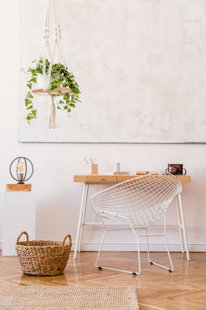 Photo for Minimalistic boho interior with design and handmade macrame shelf planter hanger for indoor plants, wooden desk, armchair, lamp, white cube and elegant accessories. Stylish home decor. White walls. - Royalty Free Image