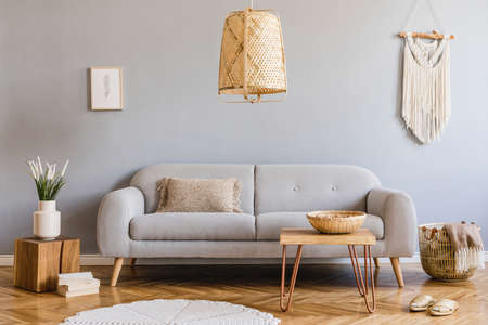 Photo pour Minimalistic and design home interior of living room with gray sofa, wooden cube,, coffee table, pillow, beige macrame, mock up poster frame and elegant accessories. Stylish home decor. Template. - image libre de droit