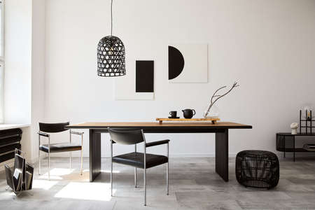 Photo pour Stylish dining room interior with design wooden family table, black chairs, teapot with mug, mock up art paintings on the wall and elegant accessories in modern home decor. Template. - image libre de droit