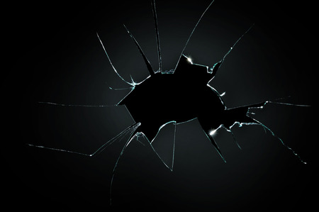 Photo for broken cracked glass with big hole over black background - Royalty Free Image