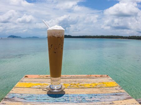 Iced coffee cappuccino in an exotic beach. Coffee on ice with beautiful sea beach on background and colorful wooden table